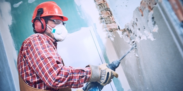Worker with personal protection equipment and demolition hammer at service for interior brick wall construction breaking in building industry